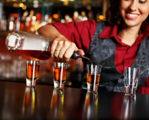 woman puring cocktail shots