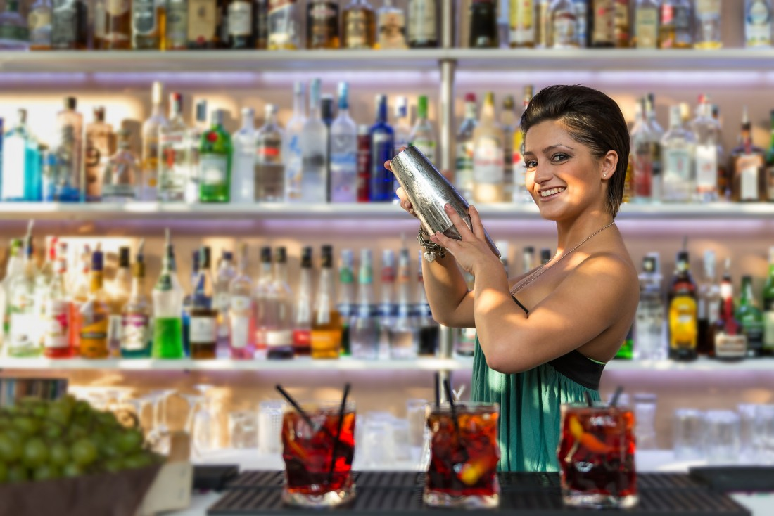 Woman bartender making cocktials in London