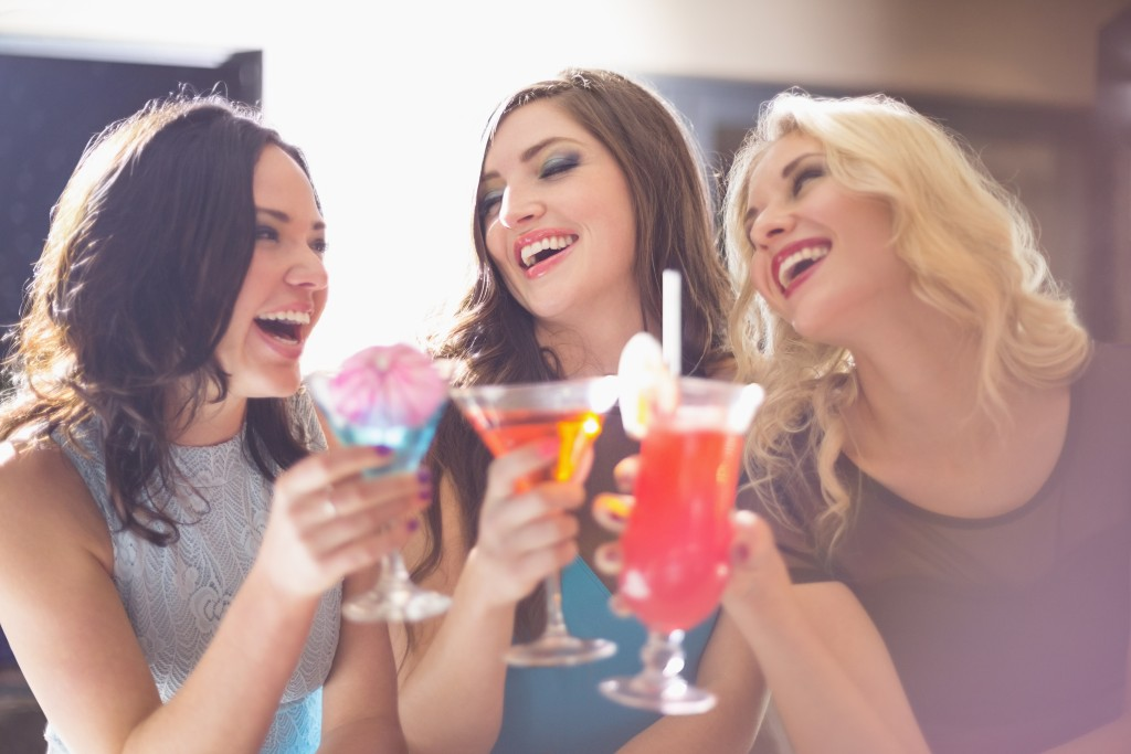 Attractive friends drinking cocktails together